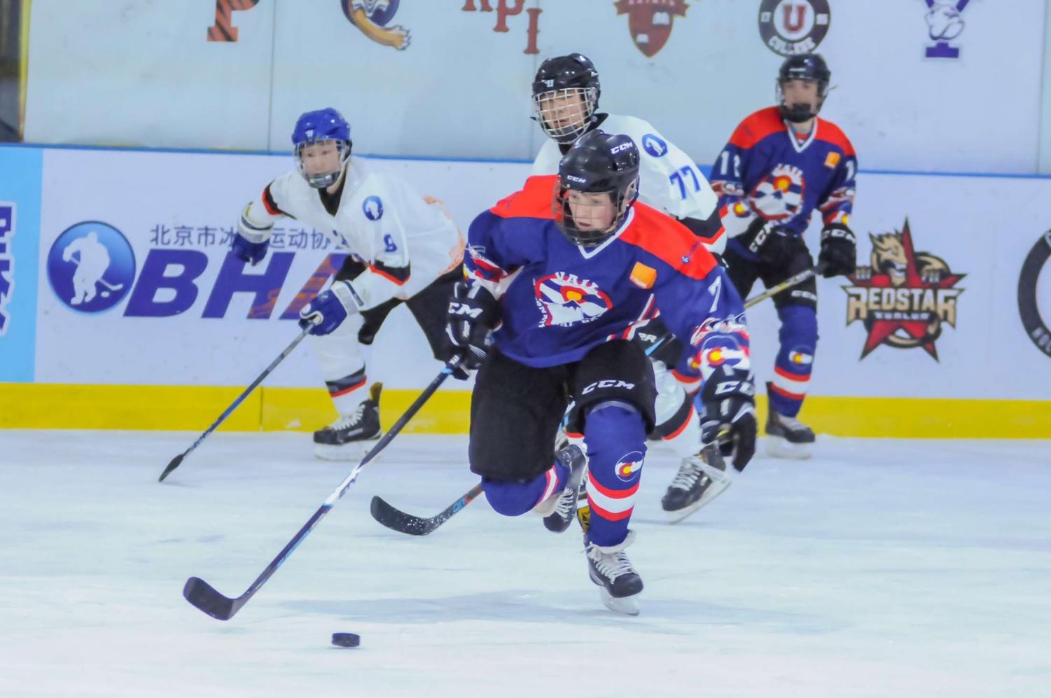Tyler Perpar carries the puck down the ice during a competitive hockey match.  Perpar was invited to play with other athletes from a collection of mountain towns in China last year.